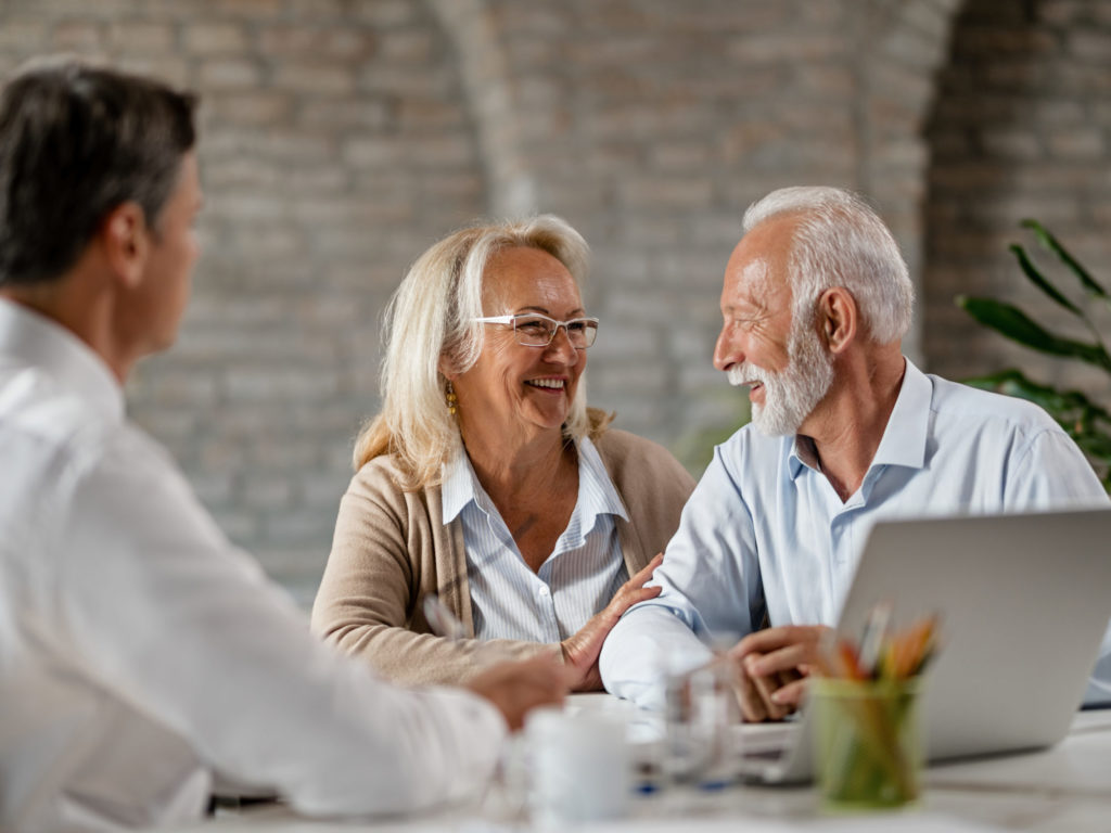 Happy senior couple talking to each other while having meeting with financial advisor.